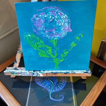 Textured purple flower with green stem and leaves on teal colored background
